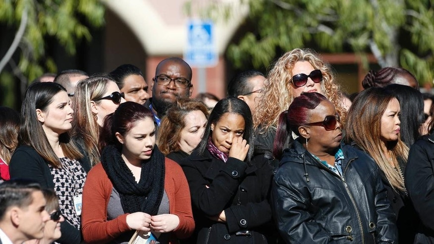 A crowd watches during a moment of silence for county workers at the Inland Regional Center in San Bernardino, Calif., Friday, Dec. 2, 2016. At the moment when shooters unleashed terror on San Bernardino a year ago, county employees remembered their fallen colleagues with a moment of silence late Friday morning. (AP Photo/Nick Ut)