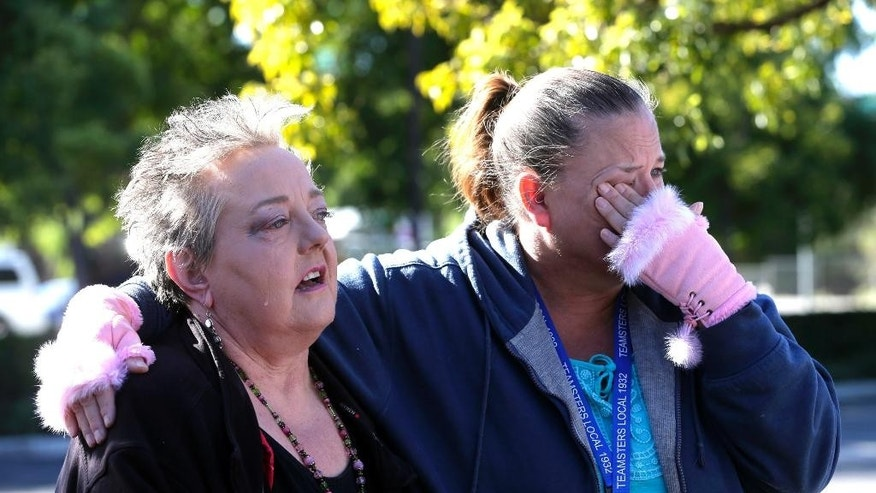 Zen Martinsen, left, stands with her friend Paula Garcia during a moment of silence for county workers at the Inland Regional Center, Friday, Dec. 2, 2016, in San Bernardino, Calif. At the moment when shooters unleashed terror on San Bernardino a year ago, county employees remembered their fallen colleagues with a moment of silence late Friday morning. (AP Photo/Nick Ut)
