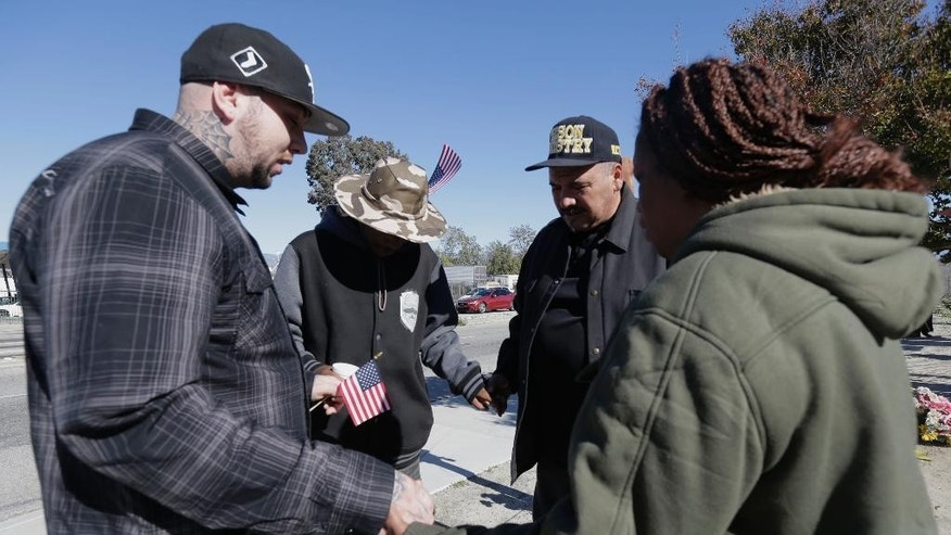 People pray during a moment of silence for county workers near the Inland Regional Center in San Bernardino, Calif., Friday, Dec. 2, 2016. At the moment when shooters unleashed terror on San Bernardino a year ago, county employees remembered their fallen colleagues with a moment of silence late Friday morning. (AP Photo/Nick Ut)