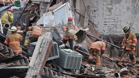Emergency crews clear debris at the scene of building collapse in Sioux Falls, S.D., Friday, Dec. 2, 2016. A fire official says rescue workers are concerned about debris shifting as they try to free two people in the collapsed building.  (Joe Ahlquist/The Argus Leader via AP)