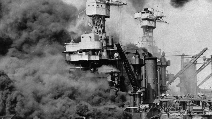 FILE - In this Dec. 7, 1941 photo made available by the U.S. Navy, a small boat rescues a seaman from the USS West Virginia burning in the foreground in Pearl Harbor, Hawaii, after Japanese aircraft attacked the military installation. More than 2,300 U.S. service members and civilians were killed in the strike which brought the United States into World War II. (U.S. Navy via AP)