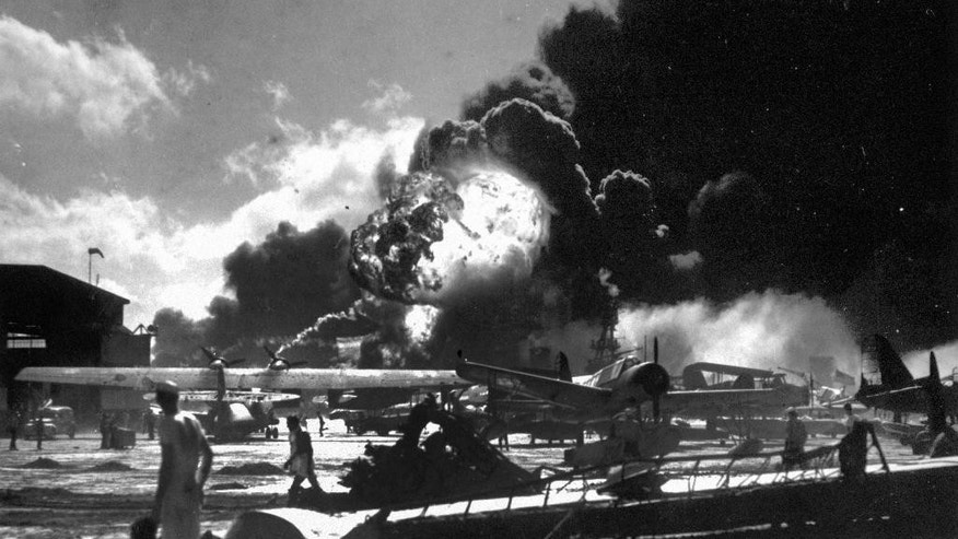 FILE - In this Dec. 7, 1941 photo provided by the U.S. Navy, sailors stand among wrecked airplanes at Ford Island Naval Air Station as they watch the explosion of the USS Shaw, background, during the Japanese surprise attack on Pearl Harbor, Hawaii. More than 2,300 U.S. service members and civilians were killed in the strike which brought the United States into World War II. (U.S. Navy via AP)