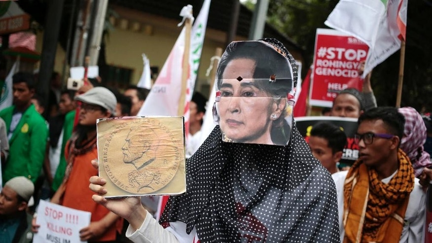FILE - In this Nov. 25, 2016, file photo, a Muslim woman wears a mask of Myanmar's Foreign Minister Aung San Suu Kyi during a rally against the persecution of Rohingya Muslims, outside the Embassy of Myanmar in Jakarta, Indonesia. It's a scene straight out of Myanmar's dark past: a military offensive waged beyond world view that forces ethnic minority villagers from the smoldering ruins of their homes. The U.S. government, a key sponsor of Myanmar's democratic transition, says a security crackdown that has displaced tens of thousands Rohingya Muslims and left an unknown number dead risks radicalizing a downtrodden people and stoking religious tensions in Southeast Asia. (AP Photo/Dita Alangkara, File)