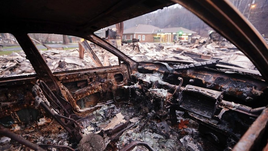 A burned car sits in a parking lot Wednesday, Nov. 30, 2016, in Gatlinburg, Tenn., after a wildfire swept through the area Monday. Three more bodies were found in the ruins of wildfires that torched hundreds of homes and businesses in the Great Smoky Mountains area, officials said Wednesday. (AP Photo/Mark Humphrey)