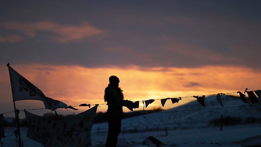 A woman watches the sunset at the Oceti Sakowin camp where people have gathered to protest the Dakota Access oil pipeline in Cannon Ball, N.D., Friday, Dec. 2, 2016.
