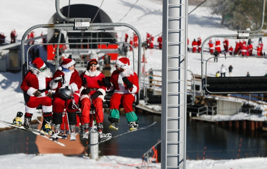 Some of the skiers dressed as Santa Claus ride the chairlift to participate in the Santa Sunday event, Sunday, Dec. 4, 2016, at the Sunday River ski resort in Newry, Maine. The event raises money for the Sunday River Community Fund, a local charity. (AP Photo/Robert F. Bukaty)