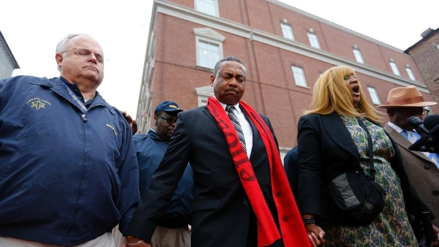 Rob Dewey, left, with the Coastal Crisis Chaplaincy and pastor Thomas Dixon, second from left, participate in a prayer vigil in front of the Charleston County Courthouse as the jury deliberates in the Michael Slager trial Monday, Dec. 5, 2016, in Charleston, S.C. Slager, the former North Charleston police officer is charged with murder in the shooting death last year of Walter Scott. (AP Photo/Mic Smith)