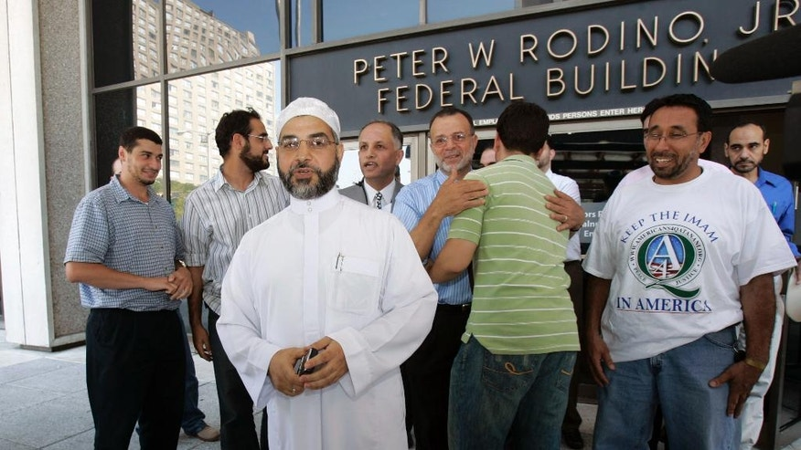 FILE In this Thursday, Sept. 4, 2008 file photograph, Imam Mohammad Qatanani, center left, walks out of the Peter W. Rodino Jr. Federal Building in Newark, N.J., with supporters, after an immigration judge ruled that Qatanani can remain in the United States. Qatanani, the leader of one of New Jersey's largest mosques is heading back to court, Monday, Dec. 4, 2016,  to fight from being deported after federal authorities say he lied on his green card application. A judge ruled against immigration authorities' attempt to have him deported eight years ago. (AP Photo/Mike Derer,file)