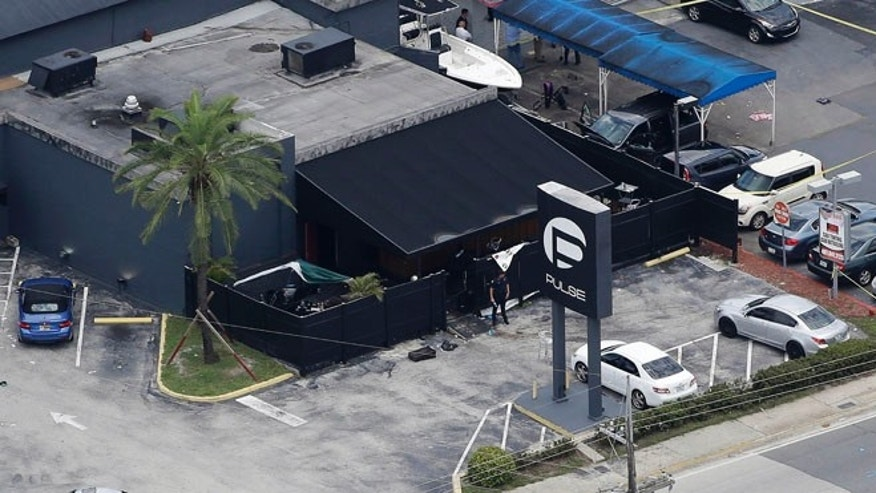 FILE - In this June 12, 2016 file photo, law enforcement officials work at the Pulse gay nightclub in Orlando, Fla., following a mass shooting.