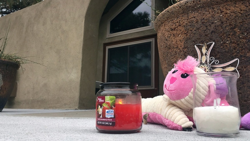A small memorial of a stuffed animal and candles left by neighbors sits outside an Albuquerque, N.M, home on Tuesday, Dec. 6, 2016, a day after police say a man broke in and fatally shot three children.