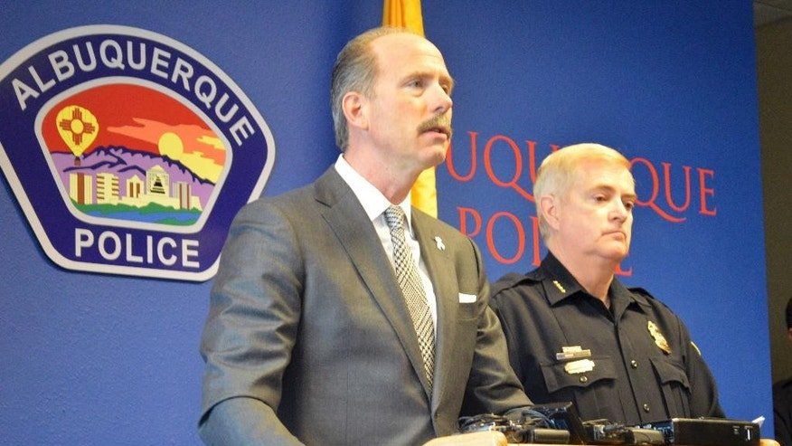 Albuquerque Mayor Richard Berry, left, speaks as  Albuquerque Police Chief Gorden Eden, right, listens during a news conference Tuesday, Dec. 6, 2016, in Albuquerque, N.M., regarding a shooting that left three children dead. Albuquerque police say the three children were killed and their mother is in critical condition after the gunman shot them when they arrived home Monday night. Authorities say the gunman was in a short relationship with the mother. (AP Photo/Russell Contreras)