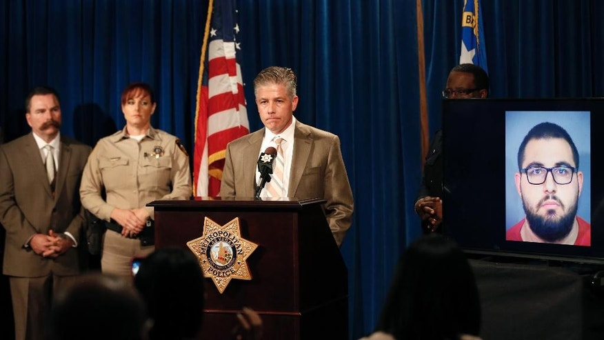 Homicide Lt. Dan McGrath speaks about 13-year-old Fabriccio Patti, who was fatally shot by clerk Raad Sunna, seen in photo at right, while attempting to rob a Las Vegas smoke shop, during a press conference at Metropolitan Police Department headquarters, on Tuesday, Dec. 6, 2016, in Las Vegas. McGrath said Sunna was arrested Monday night after police reviewed surveillance video from inside the smoke shop recorded during the Friday shooting and determined the man's life was not in danger.   (David Guzman /Las Vegas Review-Journal via AP)