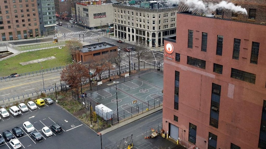 In this Nov. 29, 2016 photo, a view of Reggie Wong Park is seen next to a steam plant, at right. The fate of the modest asphalt court near where Boston Chinatown immigrants created a unique style of volleyball is uncertain. The state is seeking proposals to develop the prime slice of real estate south of downtown that's home to Reggie Wong Park, a steam plant and a state government office. The park is the latest battleground in the long-simmering debate over gentrification in one of the nation's oldest and largest Chinatowns. (AP Photo/Elise Amendola)