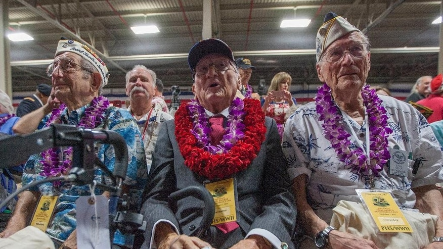 Milton Mapou, left, of the USS Detroit, Donald Stratton, center, of the USS Arizona, and Thomas Berg, right, of the USS Tennessee wait for the start of the opening ceremony for the 75th anniversary of the Japanese attack on Pearl Harbor on Kilo Pier at Joint Base Pearl Harbor-Hickam, Wednesday, Dec. 7, 2016, in Honolulu. Survivors of the Japanese attack, dignitaries and ordinary citizens attended a ceremony to commemorate the 75th anniversary of the Japanese attack on the naval harbor. (AP Photo/Eugene Tanner)