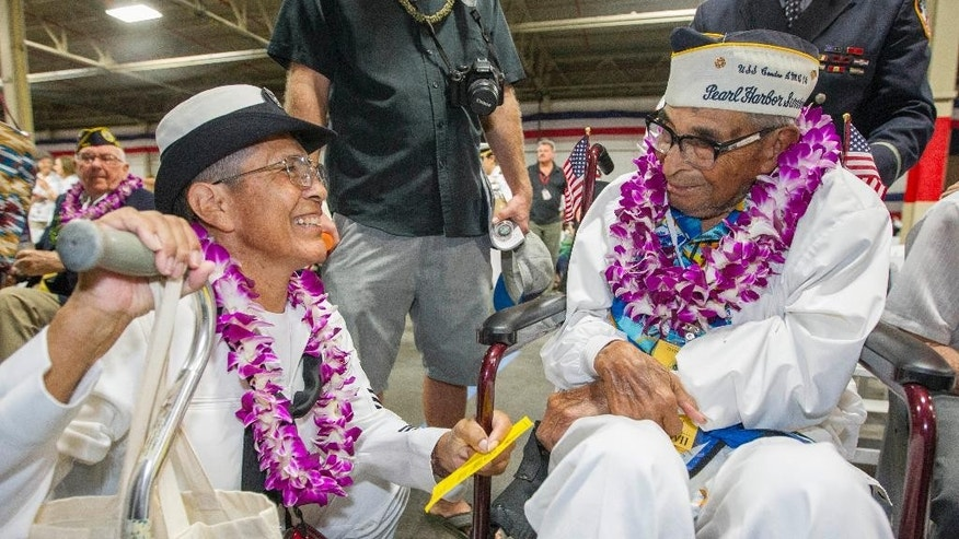 Kathleen Chavez, left, talks with her father Ray Chavez, right, age 104, of the USS Condor the oldest living survivor from the Pearl Harbor attacks along with the remaining living survivors of the USS Arizona gathered at the World War II Valor in the Pacific National Monument at Joint Base Pearl Harbor-Hickam, Wednesday, Dec.7, 2016, in Honolulu. Survivors of the Japanese attack, dignitaries and ordinary citizens attended a ceremony at Kilo Pier to commemorate the 75th anniversary of the Japanese attack on the naval harbor. (AP Photo/Eugene Tanner)