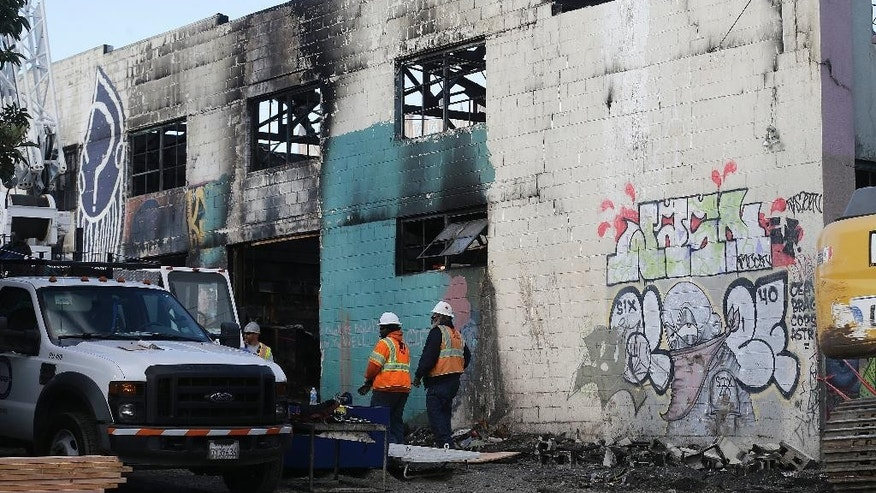 Emergency crew workers walk in front of the site of a warehouse fire in Oakland, Calif., Tuesday, Dec. 6, 2016. The fire erupted Friday, Dec. 2, killing dozens. (AP Photo/Jeff Chiu)