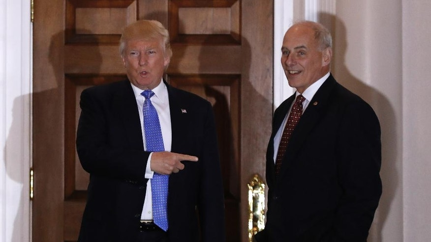 FILE - In this Nov. 20, 2016 file photo, President-elect Donald Trump talks to media as he stands with retired Marine Gen. John Kelly, at the Trump National Golf Club Bedminster clubhouse in Bedminster, N.J. Trump is tapping another four-star military officer for his administration. He has picked Kelly to lead the Homeland Security Department, according to people close to the transition. (AP Photo/Carolyn Kaster, File)