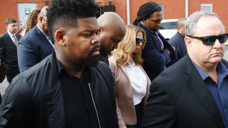"Racquel Smith, middle, widow of former New Orleans Saints NFL player Will Smith, walks to Orleans criminal court, Tuesday, Dec. 6, 2016, in New Orleans, with friends and family, after a lunch break in the trial for Cardell Hayes, who shot and killed Smith and wounded Racquel. Attorneys on both sides have suggested that Louisiana's ""stand your ground"" law will be at issue during the trial of Hayes, 29, who faces life in prison if convicted of second-degree murder. He's also charged with attempted murder after wounding Mrs. Smith. (AP Photo/Gerald Herbert)"