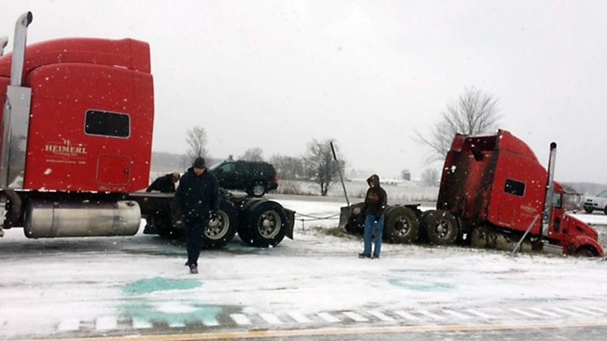 Chains are attached to semi-tractor rig as another rig gets set to try and pull it out of a ditch along Interstate 96 in Fowlerville, Mich., Thursday, Dec. 8, 2016. Michigan State Police are blaming slippery conditions for the crash. (Paula Gardner/The Ann Arbor News via AP)