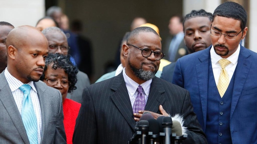 Anthony Scott, Walter Scott's brother, speaks during a press conference in front of the Charleston County Courthouse, as the family attorneys, Chris Stewart, left, and Justin Bamberg, right, watch after the mistrial was declared for the Michael Slager trial Monday Dec. 5, 2016, in Charleston, S.C. Former patrolman, Slager, was charged with murder in the April 4, 2015, shooting death of 50-year-old Walter Scott. (AP Photo/Mic Smith)