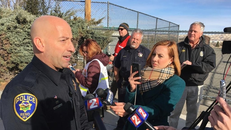 Reno police officer Tim Broadway briefs reporters outside Hug High School on the north side of Reno, Nev., on Wednesday, Dec. 7, 2016 after a Washoe County School District police officer shot a student following a disturbance at the school. The student was taken to a Reno hospital where there was no immediate word on the student's condition. (AP Photo/Scott Sonner)