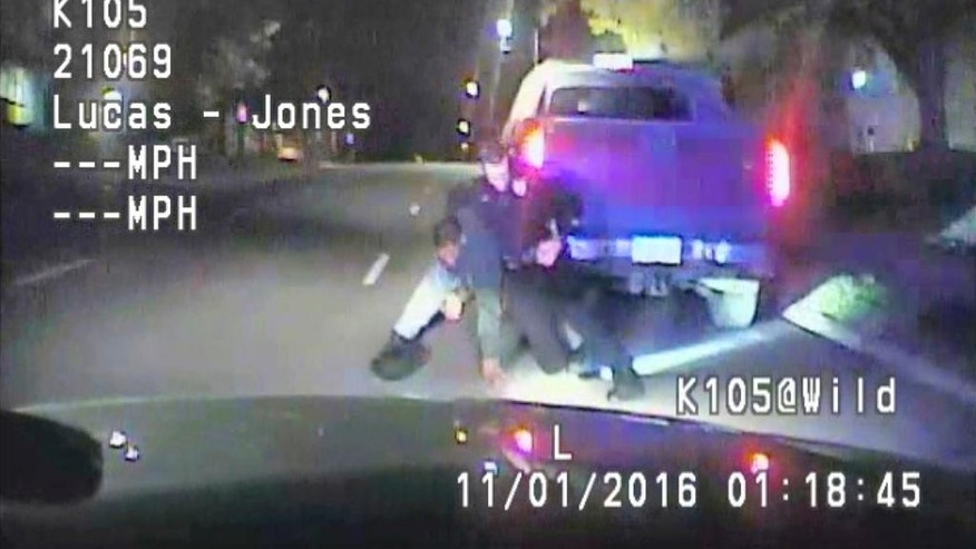 In this image made from a Nov. 1, 2016 dashcam video released Thursday, Dec. 8, 2016, by Cedar Rapids Police Department, an unarmed black motorist struggles with an Iowa officer and a police dog before the driver is shot and paralyzed. The video shows that 37-year-old Jerime Mitchell rushes back to his pickup truck and Cedar Rapids officer Lucas Jones shoots him as the vehicle rolls away. (Cedar Rapids Police Department via AP)