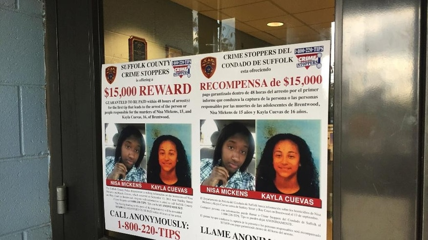 FILE - In this Oct. 24, 2016 file photo, a poster displayed at a Suffolk County police precinct in Bay Shore, N.Y., offers a $15,000 reward for information leading to the arrest of the person(s) responsible for the slayings of 15-year-old Nisa Mickens and her lifelong friend 16-year-old Kayla Cuevas. Just months ago, advocates for immigrants were lamenting publicly that a string of disappearances of Hispanic high school students in Brentwood, New York, hadn't gotten enough attention from authorities while they were happening. Now, they are worried that the president-elect's attention will mean a crackdown that goes far beyond gangs. (AP Photo/Michael Balsamo, File)