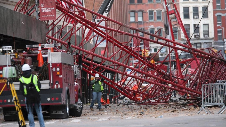 FILE- In this Feb. 6, 2016 file photo, firefighters and construction crews work on clearing up after a construction crane collapsed in New York. The New York City Department of Buildings said Friday, Dec. 9, 2016, that the crane operator failed to secure the 565-foot crane the night before it collapsed in Tribeca on Feb. 5. The department says the operator also lowered the crane's main boom at an improper angle, causing the crane to become unstable and topple over. One person died in the accident. (AP Photo/Mary Altaffer)
