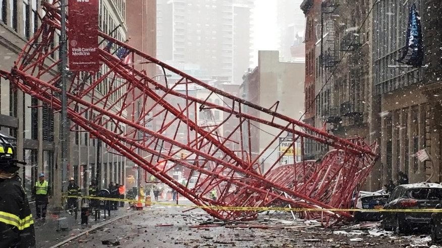 FILE- In this Feb. 5, 2016 file photo, debris and a mangled crane lie in the street in New York's Tribeca neighborhood in Lower Manhattan following a deadly collapse. The city Department of Buildings said Friday, Dec. 9, 2016, that the crane operator failed to secure the 565-foot crane the night before it collapsed in Tribeca on Feb. 5, killing one person. The department says the operator also lowered the crane's main boom at an improper angle, causing the crane to become unstable and topple over. (AP Photo/Colleen Long, File)