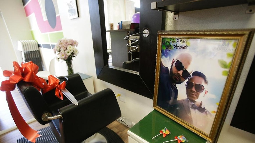 A photo of Pulse nightclub shooting victims Luis Daniel Conde, left, and Juan Rivera Velazquez rests on a shelf near the chair that Velazquez styled hair, at the D'Magazine Salon, Thursday, Dec. 8, 2016, in Orlando, Fla. Jessica Silva, Velazquez's sister in re-opening the salon to honor her brother. (AP Photo/John Raoux)