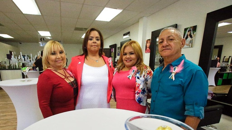 Family members of Pulse nightclub shooting victim Juan Rivera Velazquez, from left, Agelita Velazquez, his mother, sister Jessica Silva, cousin Rosa Velazquez and father Ramon Rivera, gather for a photo at the re-opening of the D'Magazine Salon Thursday, Dec. 8, 2016, in Orlando, Fla. (AP Photo/John Raoux)