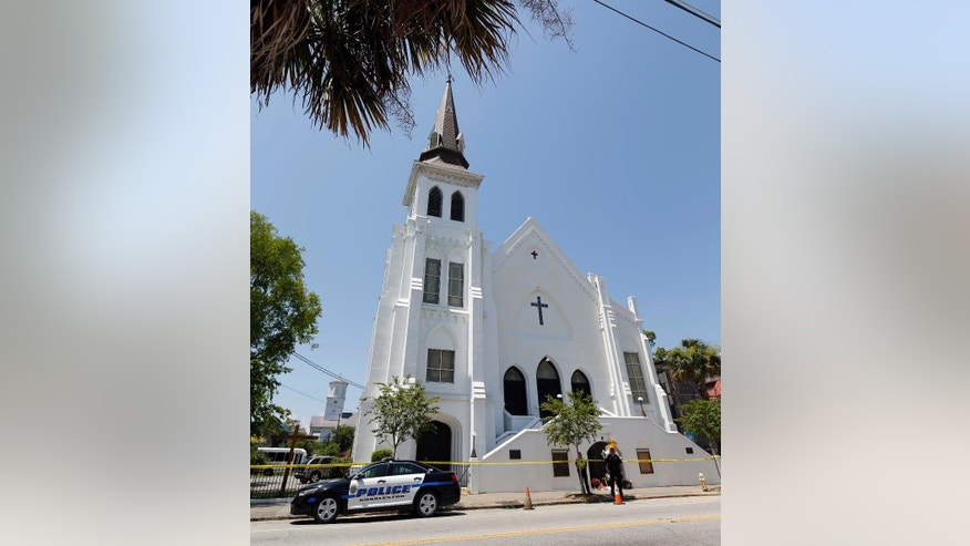 FILE- In this June 18, 2015 file photo, two Charleston police officers stand in front of the Emanuel AME Church in Charleston, S.C. The trial for Dylann Roof, a white man accused of killing nine black people at the church, started Wednesday, Dec. 7, 2016,  at the federal courthouse in Charleston, SC. (AP Photo/Stephen B. Morton, File)