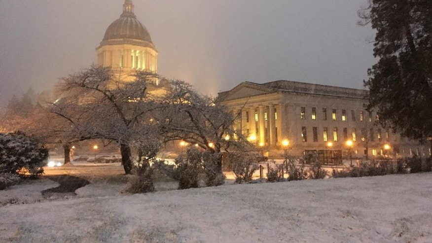 In this photo taken on Thursday, Dec. 8, 2016, the Washington Capitol is seen at sunset as snow falls in Olympia, Wash. Snow fell across the Pacific Northwest as the first winter storm of the season hit the region. (AP Photo/Rachel La Corte)