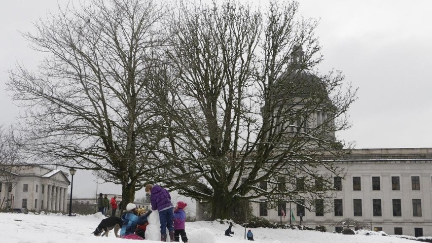 Children build a snowman on the Capitol campus in Olympia, Wash., on Friday, Dec. 9, 2016. Snow fell across the Pacific Northwest as the first winter storm of the season hit the region. (AP Photo/Rachel La Corte)