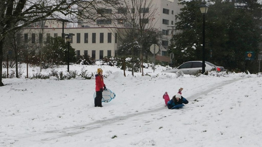 Children sled down a hill at the Capitol campus in Olympia, Wash., on Friday, Dec. 9, 2016. Snow fell across the Pacific Northwest as the first winter storm of the season hit the region. (AP Photo/Rachel La Corte)