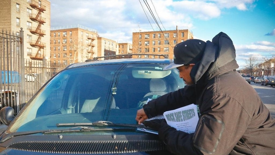 Visol Smith, center, a directing supervisor with Rock Safe Streets, a gun violence intervention program in Far Rockaway run by the nonprofit Sheltering Arms, place flyers about the program's latest anti-violence campaign on neighborhood cars, Friday Dec. 9, 2016, in New York.  Even as homicide rates have climbed in other American cities, New York City is again on pace to have a near-record low number of shootings, and police are partly crediting refined tactics that include collecting more data and forensic evidence than ever before to go after the worst offenders. (AP Photo/Bebeto Matthews)