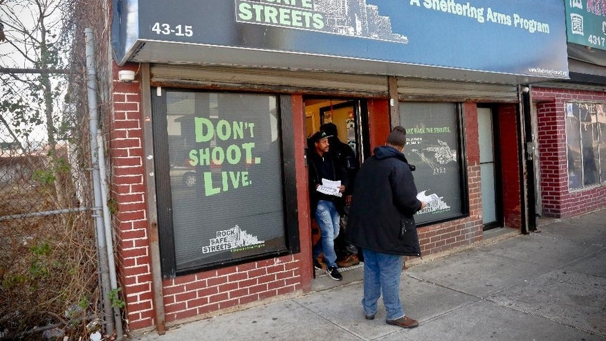 "Community outreach workers leave the office of Rock Safe Streets, a gun violence intervention program in Far Rockaway run by the nonprofit Sheltering Arms, to ""get the word"" out about their campaigns to stop the violence, Friday Dec. 9, 2016, in New York.  Even as homicide rates have climbed in other American cities, New York City is again on pace to have a near-record low number of shootings, and police are partly crediting refined tactics that include collecting more data and forensic evidence than ever before to go after the worst offenders. (AP Photo/Bebeto Matthews)"