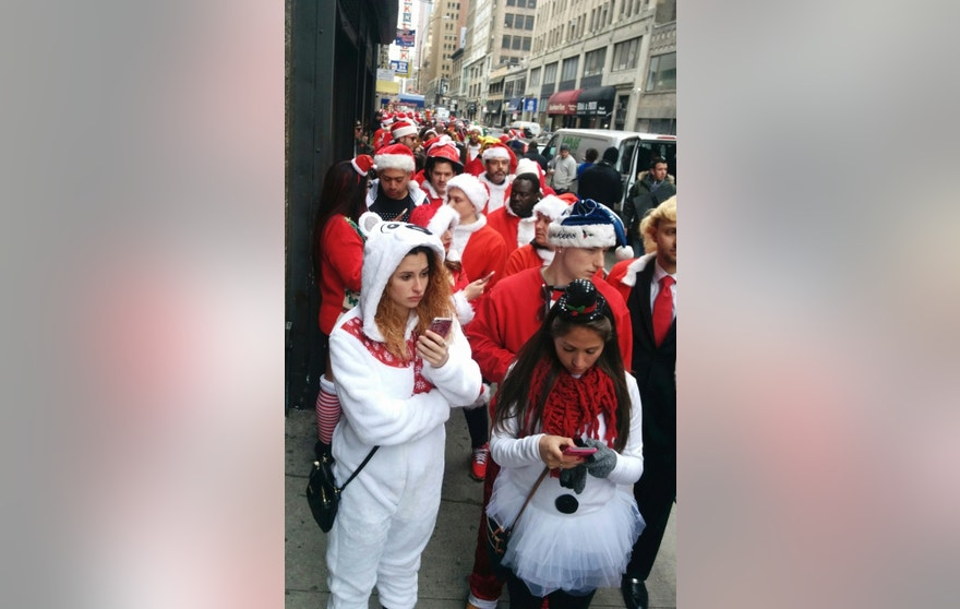 "Revelers line up to enter a tavern during the annual ""SantaCon"" in New York on Saturday, Dec. 10, 2016.  SantaCon grew from a 1994 San Francisco ""Santarchy"" that satirized Christmas consumerism into bashes in over 300 cities. (AP Photo/Julie Walker)"