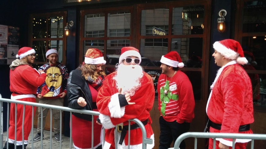 Revelers line up to enter a tavern for the 2016 SantaCon celebration in New York, Saturday, Dec. 10, 2016. New York City's annual SantaCon event is on despite efforts by a community group to deter the holiday pub crawl by red-suited revelers. (AP Photo/Julie Walker)