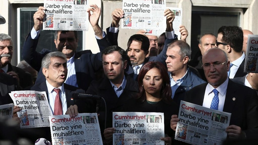 FILE - In this Oct. 31, 2016, file photo, Journalists and lawmakers hold a latest copy of Cumhuriyet newspaper outside its Istanbul headquarters after police detained chief editor Murat Sabuncu and two columnists of Turkey's opposition Cumhuriyet newspaper and had warrants to detain 10 other senior staff members, in Istanbul, Turkey. In a two-month period, Turkish President Recep Tayyip Erdogan's government detained more than 100 journalists and closed down at least 100 news outlets, a report by the Committee to Protect Journalists, said on Tuesday, Dec. 12. (AP Photo/Emrah Gurel, File)
