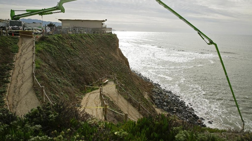A pump is used to deliver concrete and sand to a sinkhole Monday, Dec. 12, 2016, in Pacifica, Calif. Large waves, known as king tides, could have caused a sinkhole that emerged over the weekend on the coast south of San Francisco. (AP Photo/Eric Risberg)
