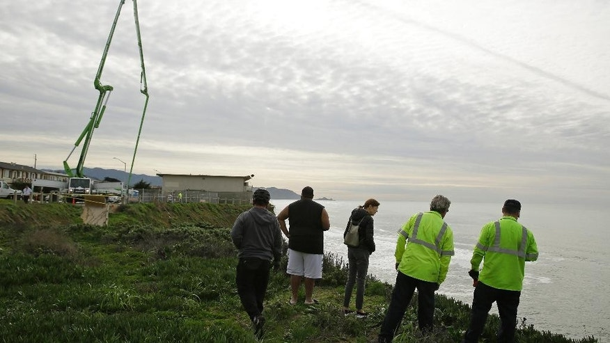 People stand at the edge of a cliff to get a view of a sinkhole Monday, Dec. 12, 2016, in Pacifica, Calif. Large waves, known as king tides, could have caused a sinkhole that emerged over the weekend on the coast south of San Francisco. (AP Photo/Eric Risberg)
