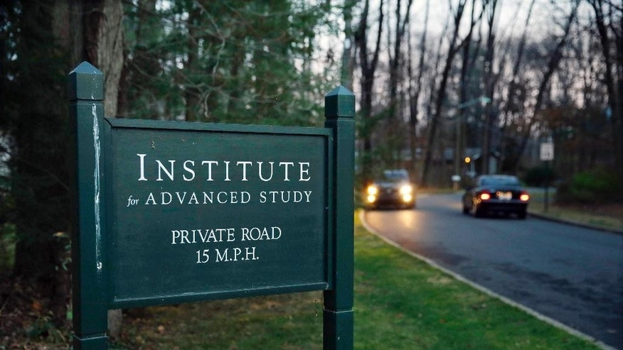 FILE - In this Dec. 10, 2015 file photo, cars pass the sign for the Institute of Advanced Study in Princeton, N.J. Historical activists have reached an agreement to save a portion of a Revolutionary War battlefield in New Jersey from development. The Civil War Trust tells The Associated Press on Monday, Dec. 12, 2016, that it will pay an academic institute $4 million for nearly 15 acres across from Princeton Battlefield State Park. (AP Photo/Mel Evans, File)