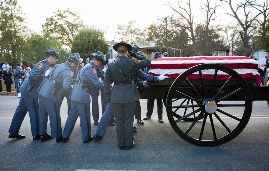 An honor guard loads the casket of Americus police officer Nicholas Smarr on to a caisson following a funeral service at the Georgia Southwestern State University Storm Dome, Sunday, Dec. 11, 2016, in Americus, Ga. Smarr and Jody Smith, an officer with Georgia Southwestern State University, were shot and killed while responding to a domestic violence call. (AP Photo/Branden Camp)