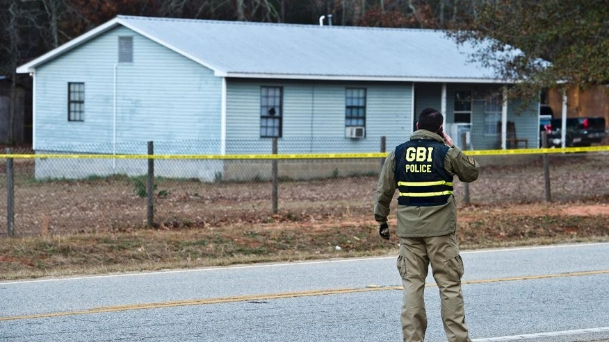 Georgia Bureau of Investigation Special Agent in Charge J.T. Ricketson works at a scene of a shooting involving multiple officers while serving a search warrant at a home in Crawford County, Ga., Monday, Dec. 12, 2016. Authorities said the suspect in the shooting at the home has died. (Woody Marshall/The Macon Telegraph via AP)