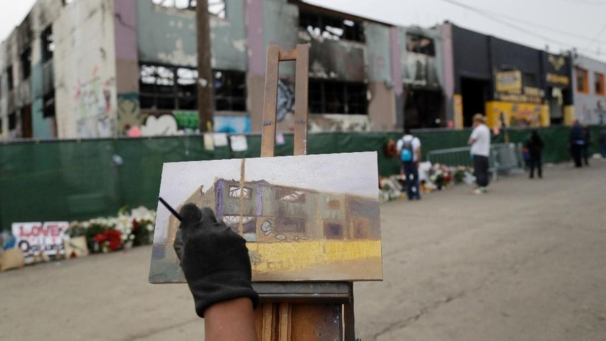 Artist John Paul Marcelo paints the scene of a warehouse fire Tuesday, Dec. 13, 2016, in Oakland , Calif. The fire killed dozens of people during a electronic dance party as it raced through the building, in the deadliest structure fire in the U.S. in more than a decade. (AP Photo/Marcio Jose Sanchez)