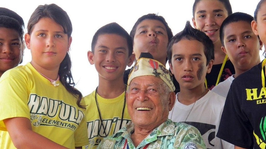 FILE - In this Nov. 22, 2013 file photo, Herb Weatherwax, then 96, poses for a photo with Hau'ula Elementary School sixth graders, from left, Dawson Langinbelik, Rachel Cheney, Frank Kojima, La'a Beatty, Chase Colleado, Makoa Ahquin-Soren and Keola Baily, as he greets visitors to the Pearl Harbor Memorial in Pearl Harbor, Hawaii. Weatherwax, an Army veteran who survived the attack on Pearl Harbor, died Monday, Dec. 12, 2016 at age 99. Weatherwax greeted people at the Memorial several times a week. (AP Photo/Audrey McAvoy, File)