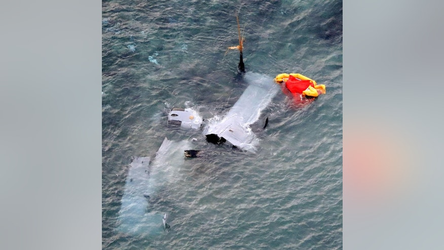 Debris of U.S. military MV-22 Osprey is seen in shallow waters off Nago, Okinawa, southern Japan, Wednesday, Dec. 14, 2016, after its crash-landing. The MV-22 Osprey, tilt-rotor aircraft deployed in Japan, crash-landed off Okinawa island late Tuesday, but all its five crew members were safely rescued. (Yusuke Ogata/Kyodo News via AP)