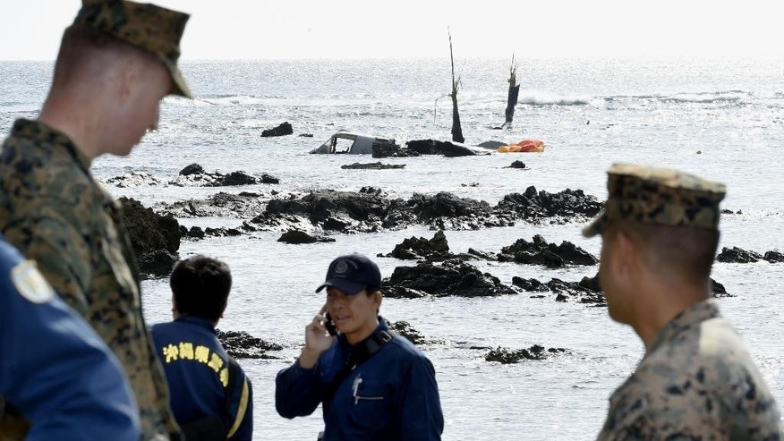 Officers of Okinawa Prefectural Police and U.S. military investigate the site where debris of a U.S. military MV-22 Osprey, background, was spotted in shallow waters off Nago, Okinawa, southern Japan, Wednesday, Dec. 14, 2016, after its crash-landing. The MV-22 Osprey, tilt-rotor aircraft deployed in Japan, crash-landed off Okinawa island late Tuesday, but all its five crew members were safely rescued. (Takumi Sato/Kyodo News via AP)