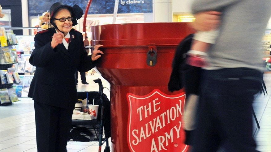 FILE - In this Nov. 15, 2014, file photo, Salvation Army bell ringer Esther Rahenkamp, of Avon Park, Fla., greets shoppers at NorthPark Mall in Davenport, Iowa, standing next to a 700-pound donation kettle. The holiday season is a great time to give, not just presents to loved ones but also to charities to help others. Donations of money or goods to a charity by the end of the year may also help you on your federal income tax return. (Gary Krambeck/The Dispatch via AP, File)